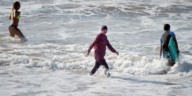 A Moroccan woman wearing a 'burkini' (C), a full-body swimsuit designed for Muslim women, enters the sea at Oued Charrat beac