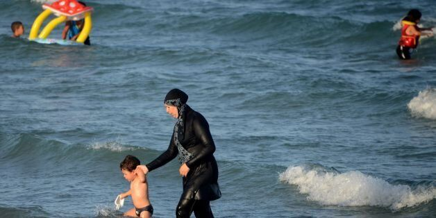 A Tunisian woman wearing a 'burkini', a full-body swimsuit designed for Muslim women, walks in the water with a child on Augu