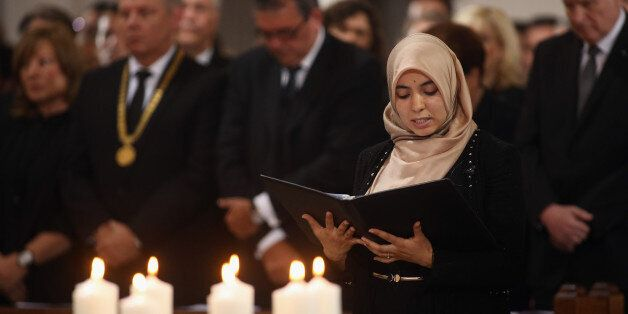 MUNICH, GERMANY - JULY 31:  A Muslim woman prays in front of nine candles symbolizing the victims of a rampage shooting durin