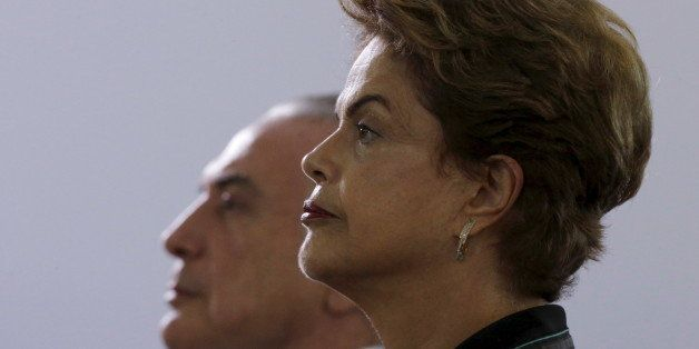 Brazil's President Dilma Rousseff (R) and Vice President Michel Temer listens to Brazil's national anthem before an annual lu