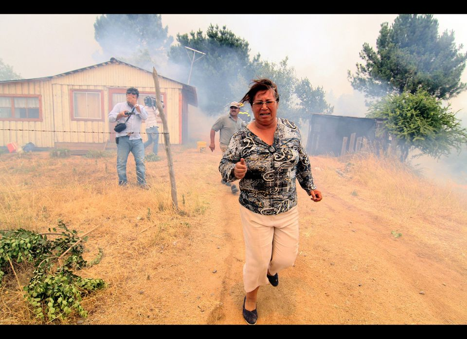 A woman runs from a massive forest fire affecting the commune of Quillon in southern Chile's Bio Bio region on Jan. 2, 2012.