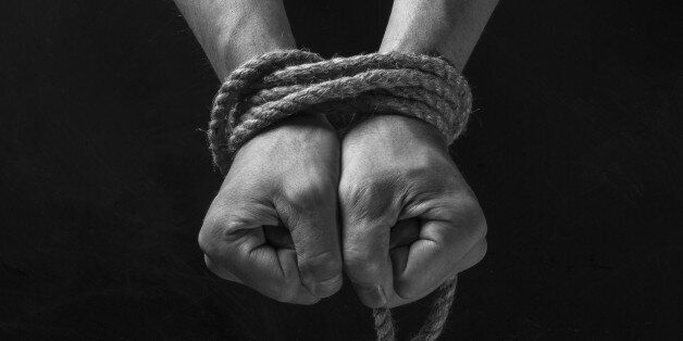 Hands tied with rope on a black background.