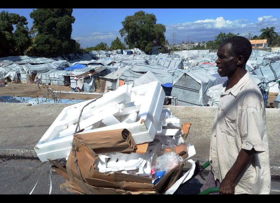 A Haitian man walks by a tent city on January 10, 2012 near Port-au-Prince. (THONY BELIZAIRE/AFP/Getty Images)