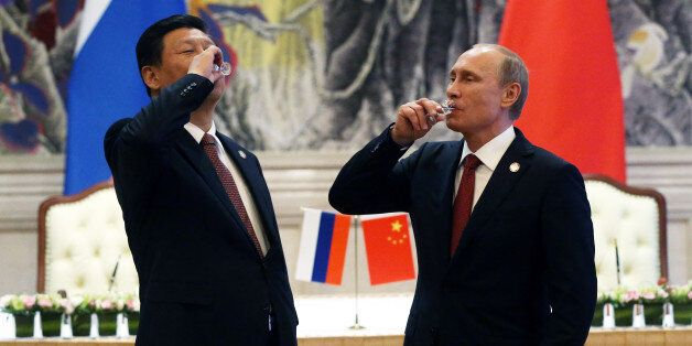 SHANGHAI, CHINA - MAY 21: President of Russia Vladimir Putin and Chinese President Xi Jinping toast with vodka during a signi