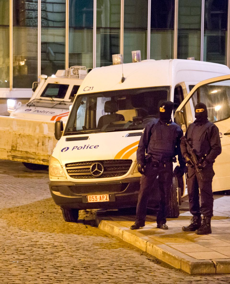 Police officer stand guard around the central police headquarters in Brussels, Thursday, Jan. 15, 2015. (AP Photo/Virginia Ma