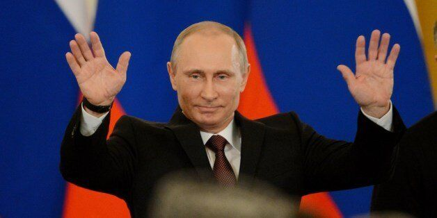 Russia's President Vladimir Putin gestures after signing a treaty on the Ukrainian Black Sea Crimea peninsula becoming part o