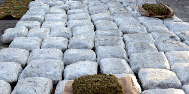 Macedonian customs officers pose for the media with hundreds of packages of marijuana which were seized at a border crossing,