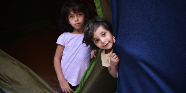 Refugee children peer out from their tent at the municipality-run Souda camp on the Greek island of Chios on September 29, 20