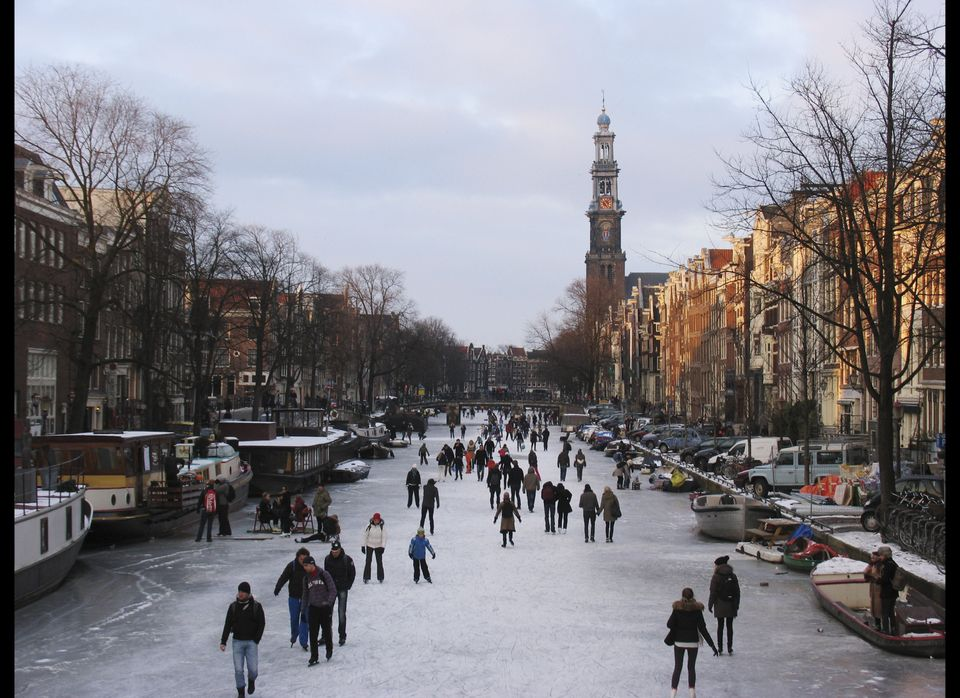 People skate on the frozen Prinsengracht canal in Amsterdam, Netherlands, Wednesday Feb. 8, 2012. In Amsterdam, several of th