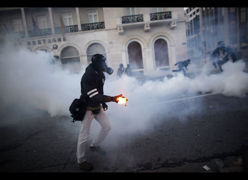 A demonstrator throws a Molotov cocktail as protesters clash with riot police in front of the parliament in Athens on Feb. 12
