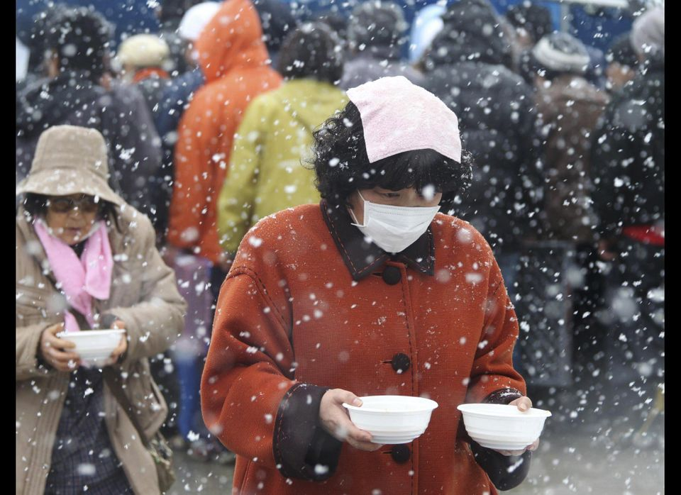 Evacuees carry bowls of soup back to their makeshift shelter in Minamisanriku, northern Japan.