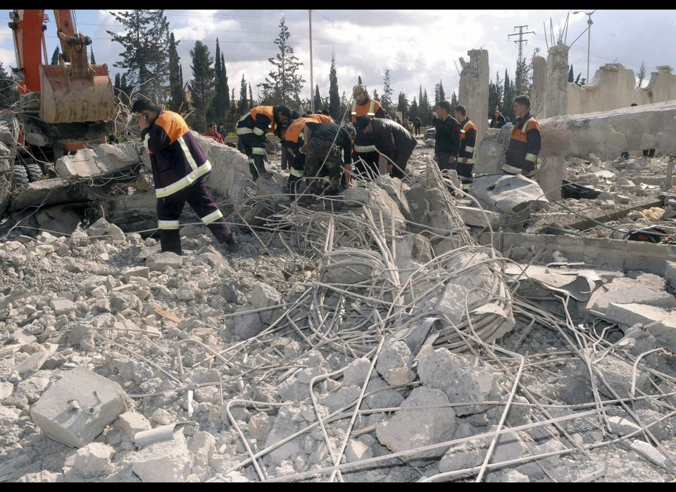 In this photo released by the Syrian official news agency SANA, Syrian rescue workers remove wreckage from a destroyed buildi