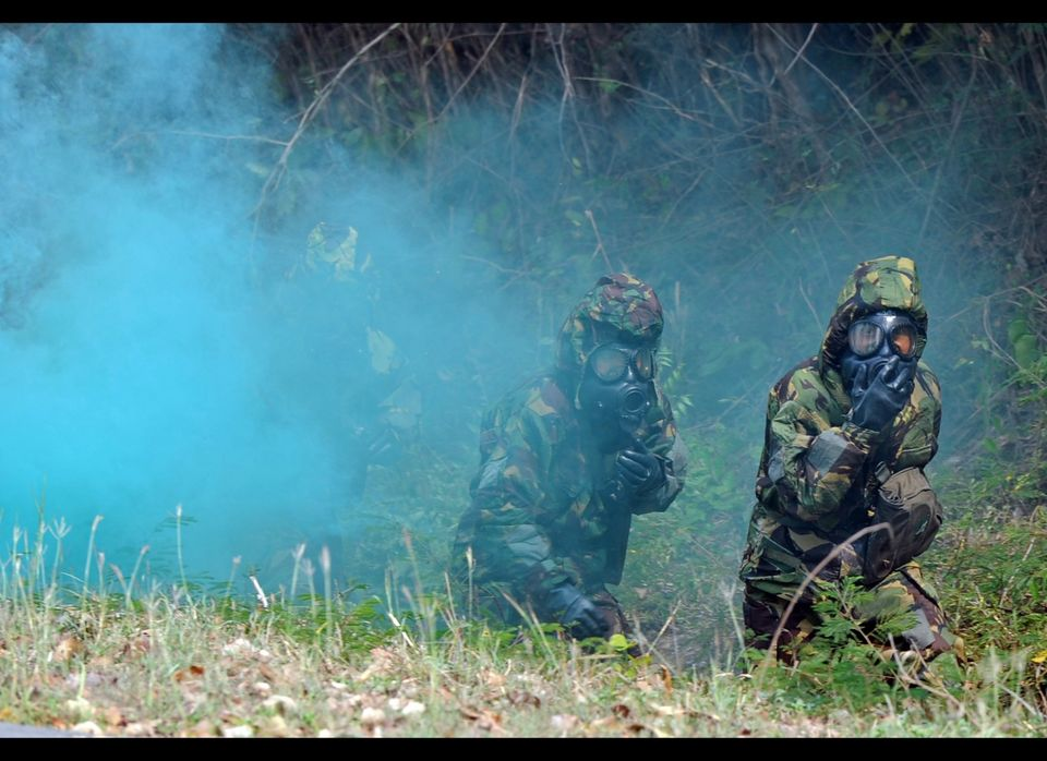 Thai soldiers wearing protection gears walk past a chemical gas during the Chemical, Biological, Radiological, Nuclear & High