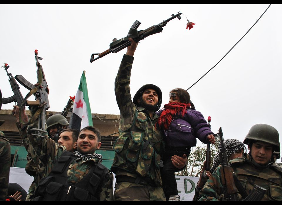 In this Thursday, Jan. 26, 201, file photo, Syrian army defectors, celebrate shortly after they defected and join the anti-Sy