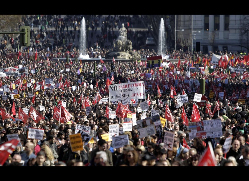 Thousands of demonstrators hold banners against the government's recently approved labor reforms during a protest in Madrid,