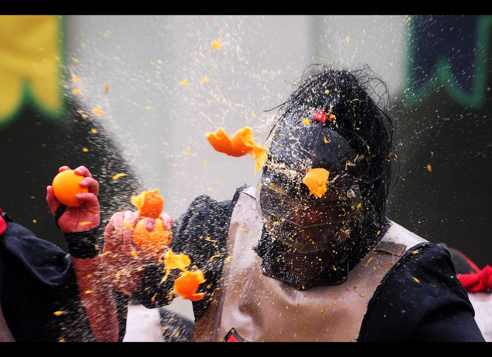 """A man with a helmet is hit by an orange during the traditional """"battle of the oranges"""", held during the carnival in Ivrea, ne"""