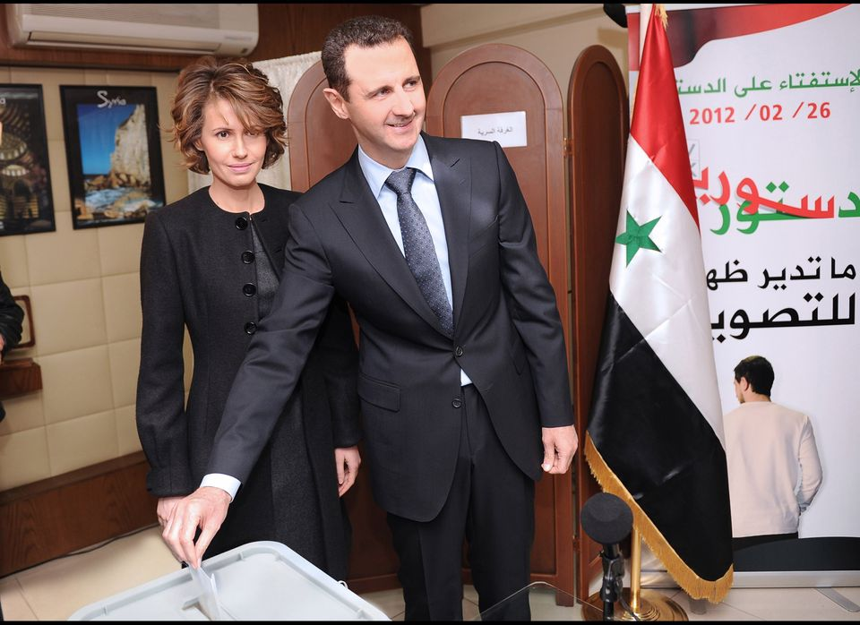 In this photo released by the Syrian official news agency SANA, Syrian President Bashar Assad casts his ballot next to his wi
