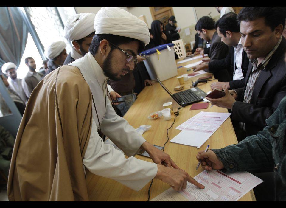 An Iranian fingerprints his ballot for the parliamentary elections at Masoumeh shrine in the city of Qom, 78 miles (125 kilom