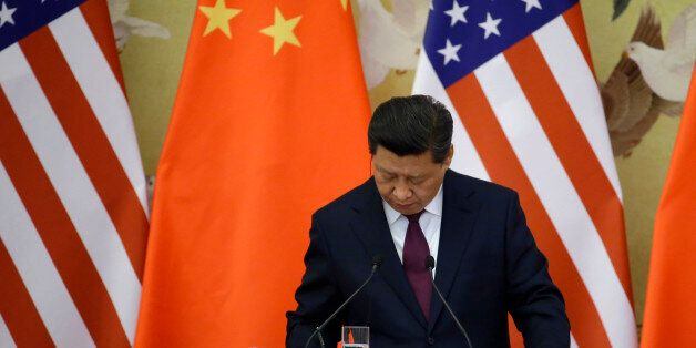 China's President Xi Jinping takes down notes as he speaks to media in front of U.S. and Chinese national flags during a join