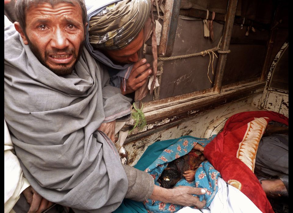A mourner cries over the bodies of Afghan civilians, allegedly shot by a rogue US soldier, seen loaded into the back of a tru