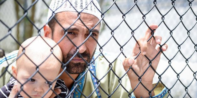 Muslim refugee holding his baby looking through a fence