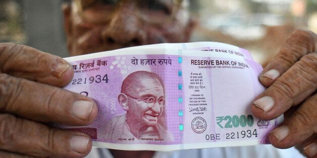 A man holds new Indian two thousand rupee banknotes for a photograph outside a bank in Dadri, Uttar Pradesh, India, on Tuesday, Nov. 15, 2016. Over a week since Prime Minister Narendra Modi shocked the nation with the withdrawal of large denomination notes there was no sign the government had managed to print enough notes to replace its withdrawal of 86 per cent of currency in circulation. Photographer: Anindito Mukherjee/Bloomberg via Getty Images