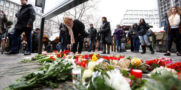People gather to lay down flowers outside the Gedaechniskirche near the area where a truck which ploughed into a crowded Chri