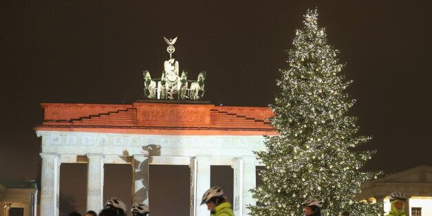BERLIN, GERMANY - DECEMBER 20:  The Brandenburg Gate stands illuminated in the colors of the Berlin flag as bicycle-mounted p