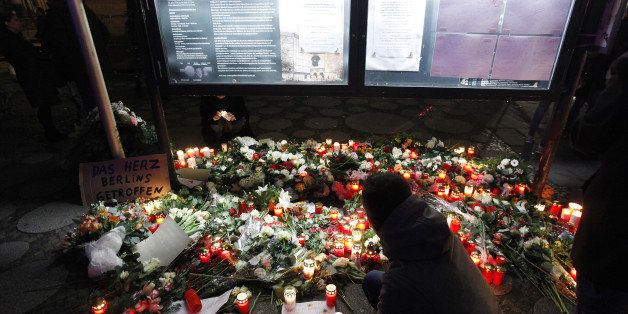 BERLIN, GERMANY - DECEMBER 20:  People leave flowers and candles at the area after a lorry truck ploughed through a Christmas