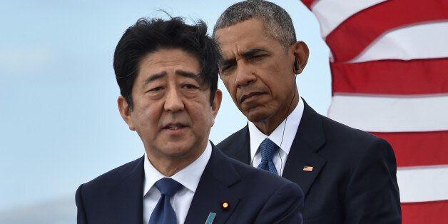 US President Barack Obama (R) listens as Japanese Prime Minister Shinzo Abe speaks at the USS Arizona Memorial on December 27