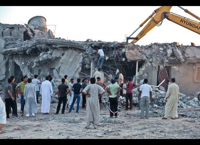 Relatives and neighbors search for survivors in the rubble of the Gafez family home in Majer on August 9, 2011, one day after