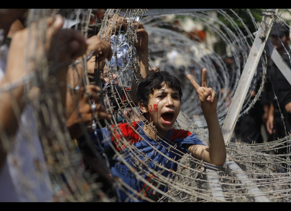 An Egyptian boy peers out of barbed wire, his face painted with the number 25, the date of the Egyptian revolution, during a
