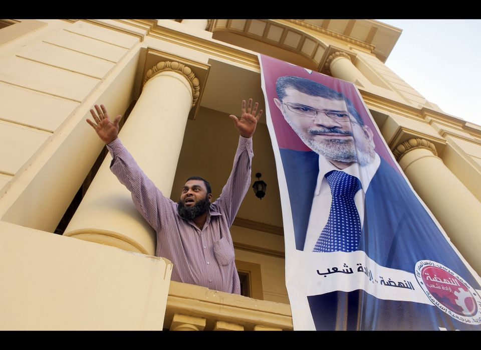An Egyptian supporter of the Muslim Brotherhood's candidate, Mohammed Morsi, celebrates next to a giant campaign poster at hi