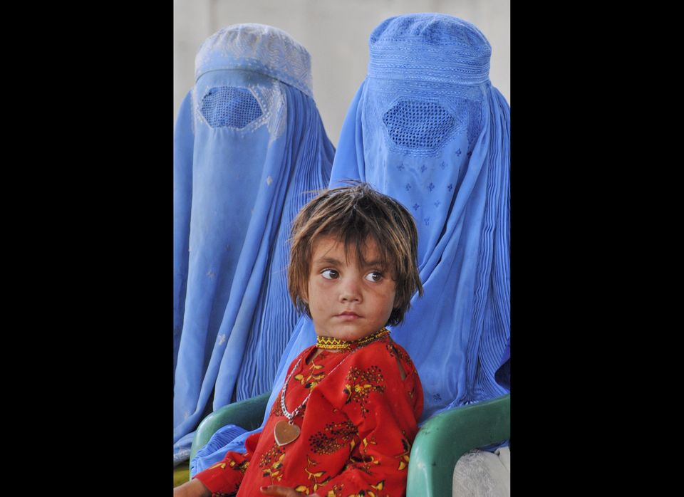 Afghan refugees wait for transport to leave for Afghanistan at a repatriation center run by the United Nations High Commissio