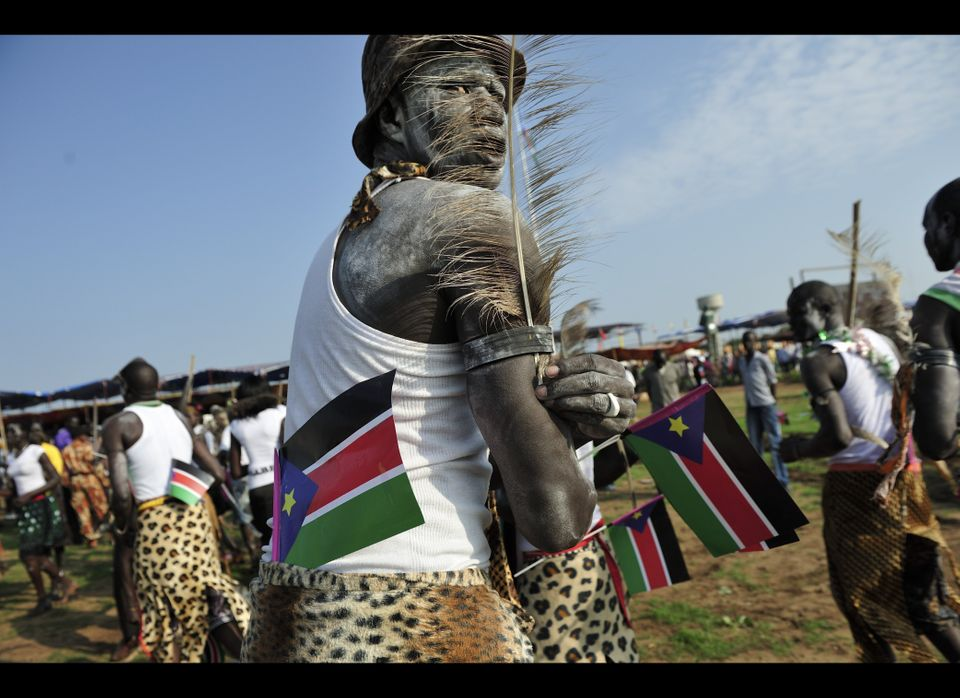A man holds South Sudanese flags as he prepares to dance at the country's anniversary celebrations, at the John Garang mausol