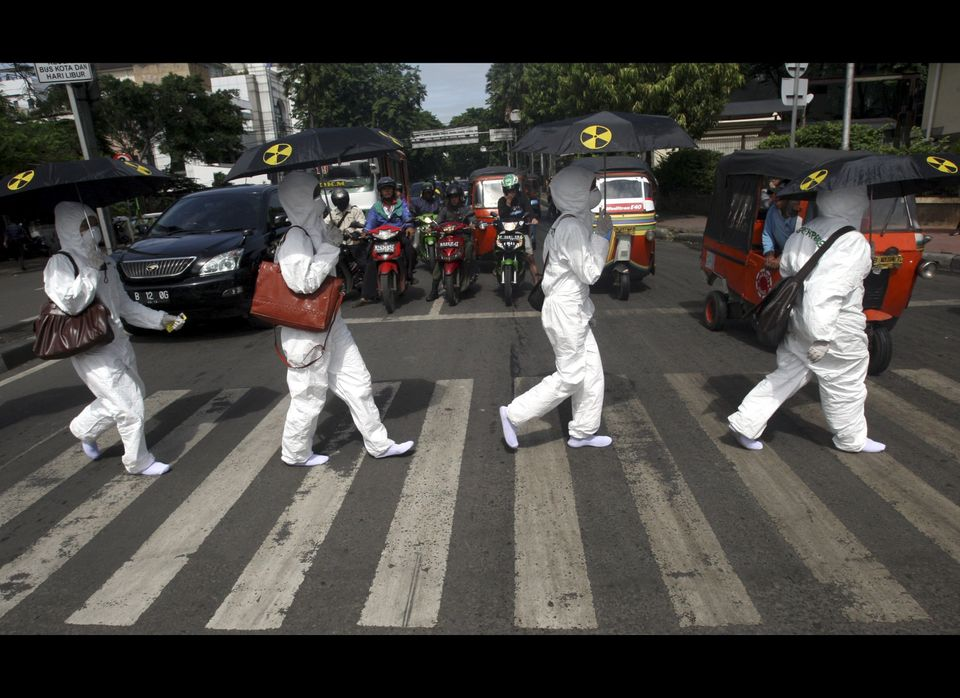 Greenpeace activists in protective suits cross a road during an anti-nuclear protest commemorating last year's earthquake and