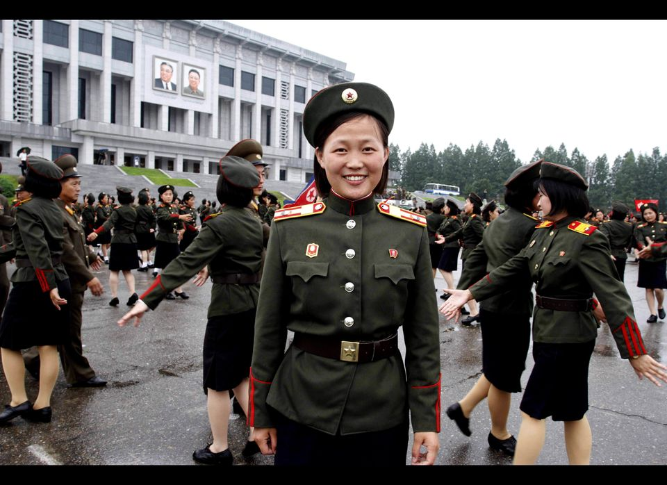 Kim Jong Gum, a 19 year-old student of Kang Pan Sok Revolutionary School, poses for the camera as North Korean soldiers dance