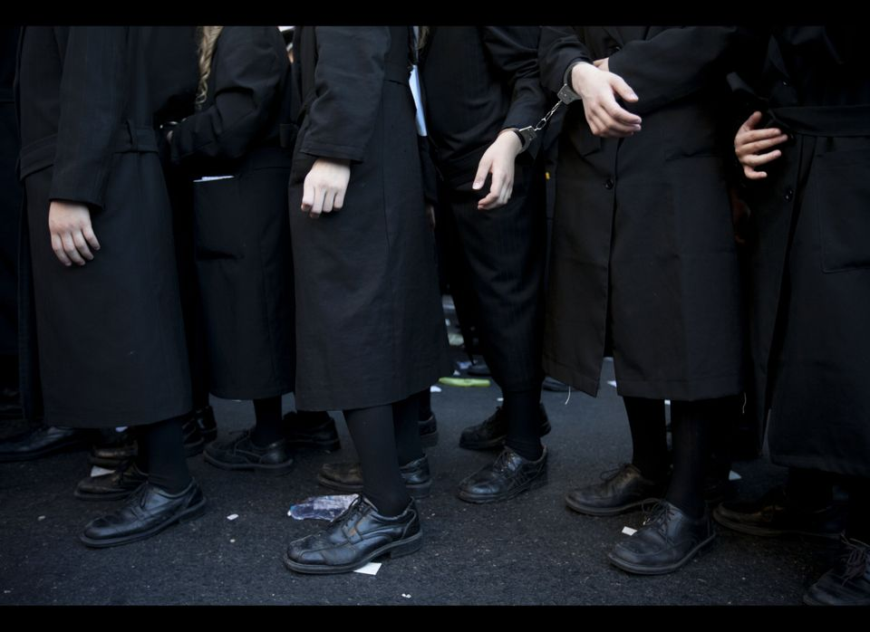 Handcuffed Ultra Orthodox Jewish men and children participate in protest against attempts to draft members of the cloistered