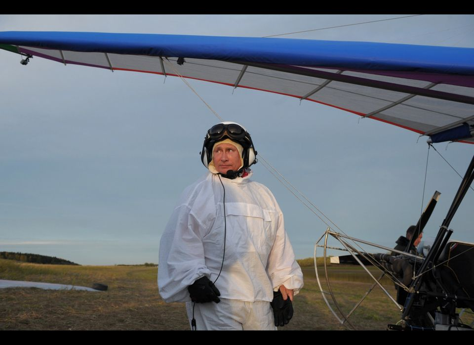 Russian President Vladimir Putin prepares to pilot a motorized hang-glider, while looking at cranes as he takes part in a sci