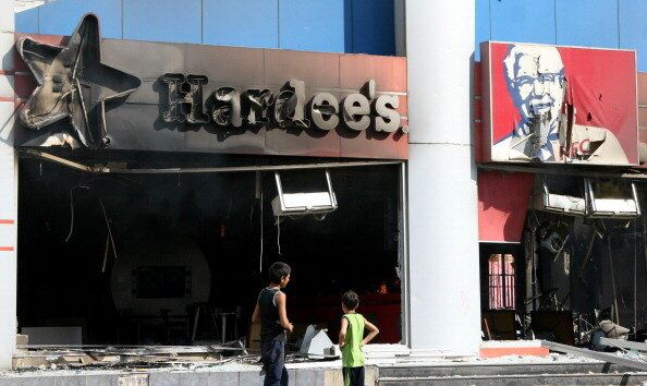 Lebanese boys inspect burnt branches of US fast food chains Hardee's and KFC after they were torched during a protest against
