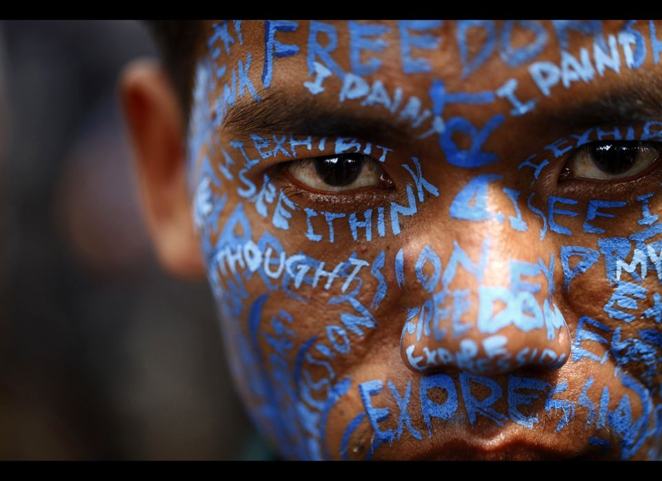 A Nepalese artist appears with his face painted during a protest outside the Katmandu District administration office in Katma