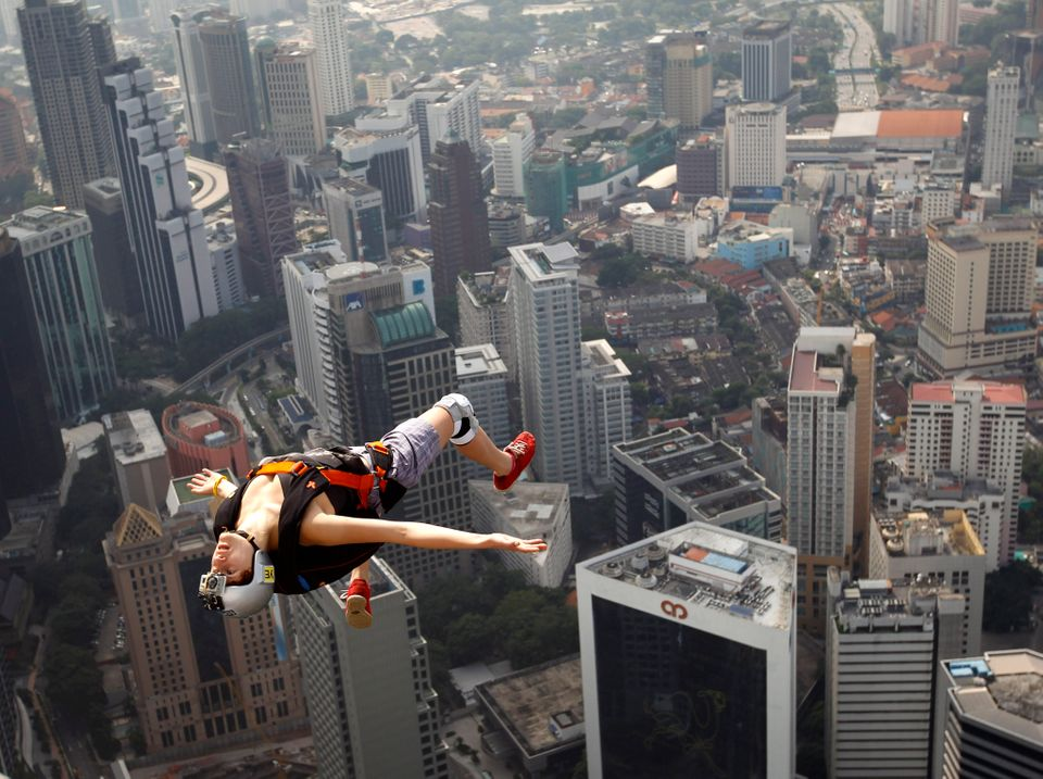 France's base jumper Florian Pays gestures while leaping from Malaysia's landmark KL Tower, the 421-meter (1,389-foot) broadc