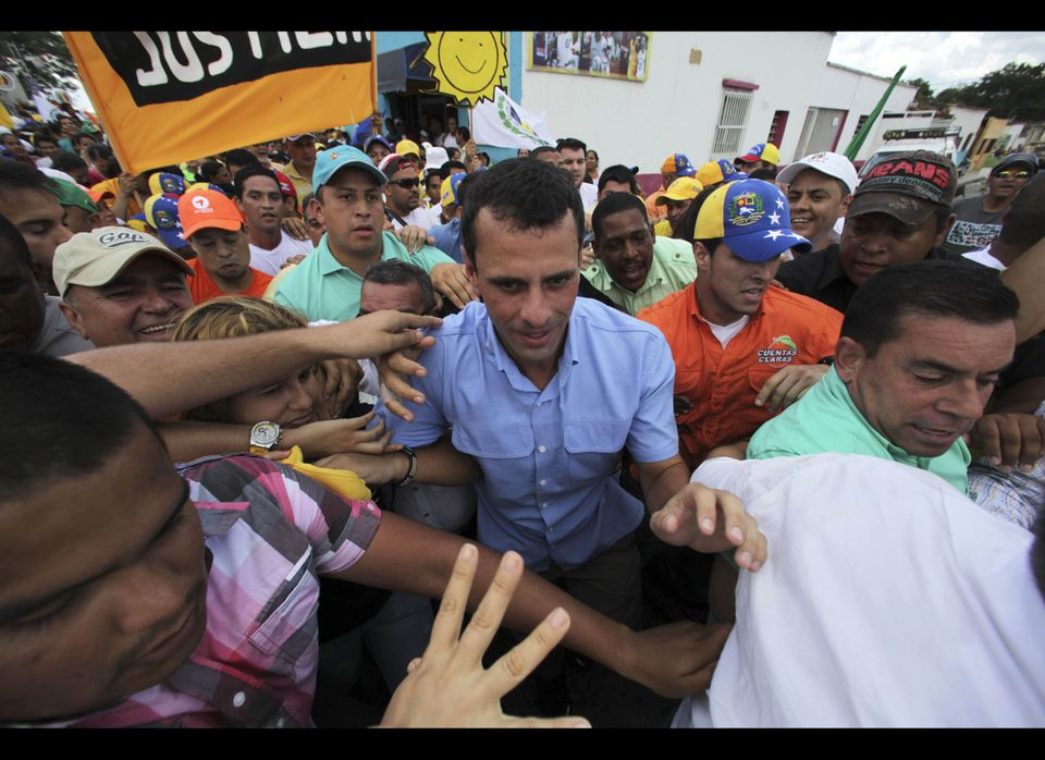 In this Sept. 1, 2012, photo, opposition presidential candidate Henrique Capriles, center, greets supporters during a campaig