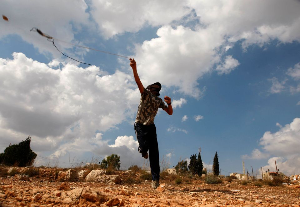 A Palestinian protester hurls stones at Israeli soldiers, not seen, during a weekly protest against the expansion of the near