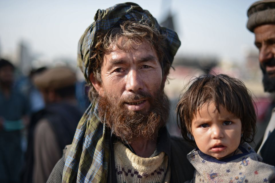 An Afghan man holds a child as he walks in downtown Kabul on October 10, 2012. (MASSOUD HOSSAINI/AFP/GettyImages)