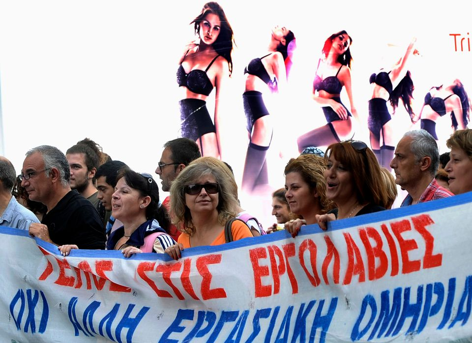 Protesters hold a banner with anti austerity slogans as they walk past an advertisement during the first day of the 48-hour n