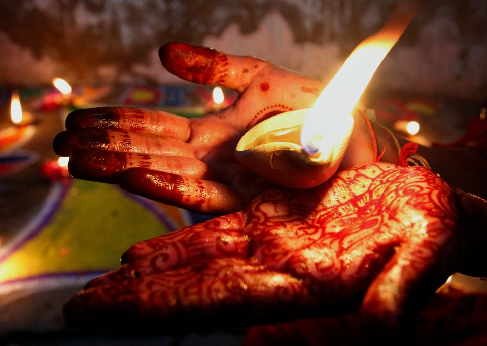 A Pakistani Hindu girl holds an earthen lamp while decorating an area of her house to celebrate Diwali, the Hindu festival of