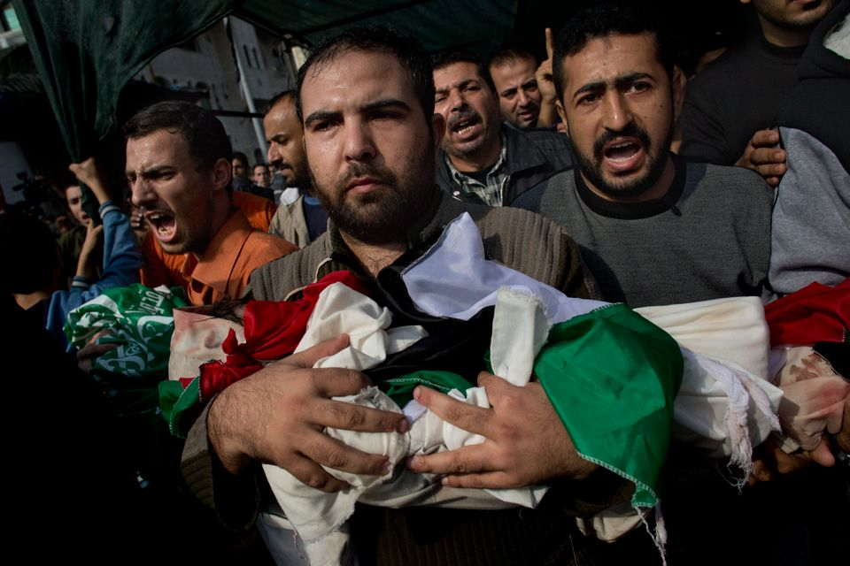 Palestinians carry bodies of members of the Daloo family during their funeral in Gaza City, Monday, Nov. 19, 2012. (AP Photo/
