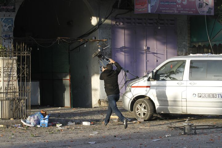 Journalists from different agencys run after an Israeli air strike on an office of Hamas television channel Al-Aqsa in Gaza C