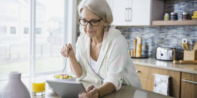Woman eating fruit salad and using digital